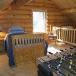 Loft with a captains bed with two singles and a great view of inside and outside the cabin.